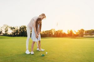 mother teaching daughter golf